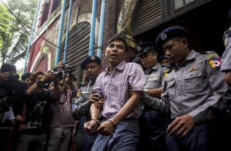 Detained Myanmar journalist Kyaw Soe Oo (C) is escorted by police out of a court in Yangon on August 27, 2018.  A Myanmar court on August 27 postponed ruling on whether two Reuters journalists violated a state secrets law while reporting on the Rohingya crisis, with a new date set for next week. / AFP PHOTO / AUNG KYAW HTET