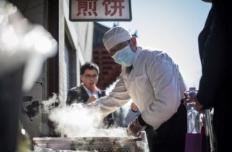 A cook prepares food for customers on a street in Beijing on March 2, 2017. / AFP PHOTO / Fred DUFOUR