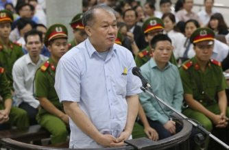 Pham Cong Danh (C, standing), former chairman of the joint stock Vietnam Construction Bank, stands trial along with former Ocean Bank chairman Ha Van Tham (2nd R, seated on first row) at the People's Court in Hanoi on August 28, 2017. A former banking magnate and 50 others went on trial in Vietnam on August 28 over a multi-million dollar fraud case at a major private bank, as the communist nation cracks down on corruption in the scandal-tainted sector.  / AFP PHOTO / Vietnam News Agency / VIETNAM NEWS AGENCY