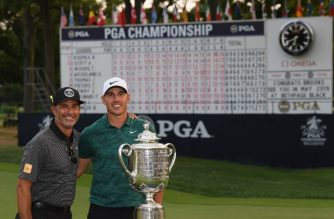 ST LOUIS, MO - AUGUST 12: Brooks Koepka of the United States poses with Claude Harmon and the Wanamaker Trophy on the 18th green after winning the 2018 PGA Championship with a score of -16 at Bellerive Country Club on August 12, 2018 in St Louis, Missouri.   Ross Kinnaird/Getty Images/AFP