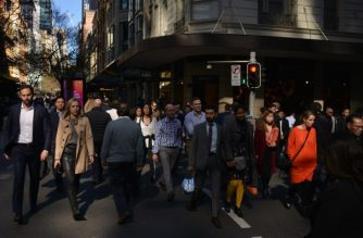 People cross a road in the central business district of Sydney on August 7, 2018. Australia's population will reach the 25 million mark on August 7, according to projections from the Australian Bureau of Statistics (ABS), a number reached in record time as net migration continues to outpace the birth rate. / AFP Photo / Peter Parks