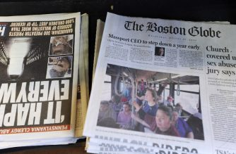 Copies of the Boston Globe sit on the shelf with other daily papers at a newspaper stand at Boston's South Station, August 15, 2018. / AFP Photo / Joseph Prezioso