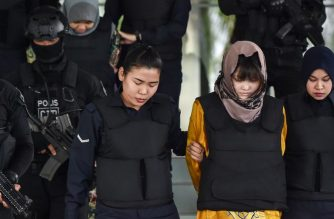 (FILES) Vietnamese national Doan Thi Huong (front, 2nd R) and Indonesian national Siti Aisyah (back, 2nd L) are escorted by Malaysian police after a court session for their trial at the Shah Alam High Court in Shah Alam, outside Kuala Lumpur on June 27, 2018 for their alleged roles in the assassination of Kim Jong Nam, the half-brother of North Korean leader Kim Jong Un. / AFP Photo / Mohd Rasfan