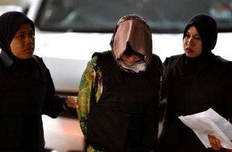 Vietnamese national Doan Thi Huong (C) is escorted by Malaysian police  along with Indonesian Siti Aisyah (not pictured) for their trial at the Shah Alam High Court, outside Kuala Lumpur on August 16, 2018 for their alleged role in the assassination of Kim Jong-Nam, the half-brother of North Korean leader Kim Jong-Un.  / AFP Photo / Manan Vatsyayana