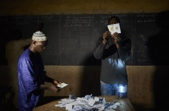 An election official shows a ballot paper during the vote counting at a polling station in Bamako on August 12, 2018, after the second round of Mali's presidential elections. / AFP Photo / Michele Cattani