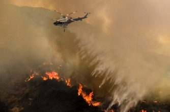 A helicopter drops water to a brush fire at the Holy Fire in Lake Elsinore, California, southeast of Los Angeles, on August 11, 2018. / AFP Photo / Ringo Chiu