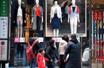 Pedestrians walk past a retail clothing shore in the Ginza shopping district in Tokyo on February 23, 2018. Japan's consumer prices edged up 0.9 percent in January, government data showed on February 23, but inflation was still far below a longstanding target. / AFP PHOTO / Kazuhiro NOGI