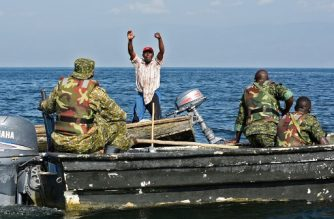 A fisherman from the Democratic Republic of Congo raises his hands up to surrender as Uganda People's Defence Marine Force (UPDMF) stop him for fishing illegally, during a patrol on the lake Edward, on August 13, 2018, in Rwenshama, in the Rukungiri District. Since the UPDMF started its operations in Lake Edward, over 400 hundred illegal fishermen from the Democratic Republic of Congo have been arrested for illegal entry into the Ugandan side. Of the 400, only 96 have so far been convicted and are serving their sentences in Ugandan prisons. / AFP PHOTO / ISAAC KASAMANI
