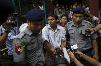Police escort detained Myanmar journalist Kyaw Soe Oo after appearing before a court trial in Yangon on August 20, 2018. At the time of their arrest Kyaw Soe Oo, 28 and Wa Lone, 32, had been investigating the massacre of 10 Rohingya Muslims in Rakhine a week after militants attacked police posts on August 25, 2017 triggering a brutal response from police and troops. / AFP PHOTO / YE AUNG THU