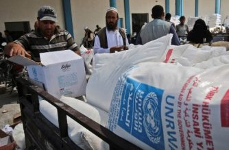 """Palestinian men collect aid food at a United Nations' compound in the Rafah refugee camp in the southern Gaza Strip on September 1, 2018. The United States announced it was halting funding for the United Nations' agency for Palestinian refugees after declaring the organisation was """"irredeemably flawed. Washington has long been the UN Relief and Works Agency's (UNRWA) largest donor but is """"no longer willing to shoulder the very disproportionate share of the burden,"""" State Department spokeswoman Heather Nauert said in a statement.  / AFP PHOTO / SAID KHATIB"""