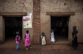 """(FILES) In this file photo taken on August 19, 2018 young Congolese girls look at a poster explaining the symptoms of Ebola in Mangina, near Beni, in the North Kivu province.  In the village of Mangina, where dozens have died of Ebola at the epicentre of Democratic Republic of Congo's latest outbreak, children are to be seen everywhere -- except in school, because their parents fear they will be infected in class. """"The children are not here today. It's the parents who are keeping them at home,"""" primary school teacher Christian Muhindo said as he paced between empty desks. """"They think that the children will be easily contaminated at school."""" / AFP PHOTO / John WESSELS"""