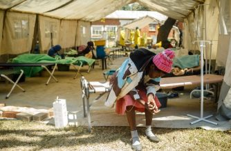 A patient receives a medication by intravenous inside a cholera treatment tent during a visit of Zimbabwe Minister of Health, at the cholera treatment centre of the Beatrice Infectious Diseases Hospital, in Harare, on September 11, 2018. At least 18 people have died over the past week in the Zimbabwe capital Harare and scores fallen ill after a cholera and typhoid outbreak in some areas, authorities said on September 10, 2018. / AFP PHOTO / Jekesai NJIKIZANA