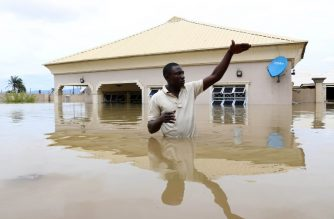A man gestures next to his flooded house following heavy rain near the Nigerian town of Lokoja, in Kogi State, on September 14, 2018. / AFP PHOTO / Sodiq ADELAKUN