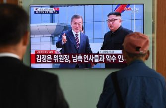 People watch a screen showing live footage of the arrival of South Korean President Moon Jae-in at Pyongyang airport as North Korean leader Kim Jong Un welcoms him, at a railway station in Seoul on September 18, 2018.  North Korean leader Kim Jong Un welcomed Moon Jae-in at Pyongyang airport on September 18, as the South Korean president arrived for the pair's third summit this year. / AFP PHOTO / Jung Yeon-je