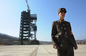 (FILES) In this file photo taken on April 8, 2012 a North Korean soldier stands guard in front of a Unha-3 rocket at the Sohae Satellite Launch Station in Tongchang-ri. North Korea will close its Tongchang-ri missile testing site, the South's President Moon Jae-in said on September 19, 2018 after a summit with Kim Jong Un in Pyongyang. / AFP PHOTO / Pedro UGARTE
