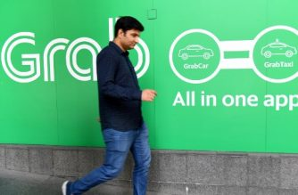 A man walks past the Grab transport office in Singapore on September 24, 2018. Singapore on September 24, fined ride-hailing firms Grab and Uber $9.5 million for breaking competition rules when they merged, saying the deal had increased fares and thrown up roadblocks for competitors. / AFP PHOTO / ROSLAN RAHMAN