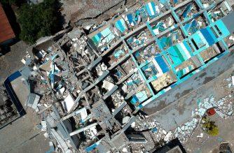 This aerial picture shows the remains of a ten-storey hotel in Palu in Indonesia's Central Sulawesi on September 30, 2018 after it collapsed following a strong earthquake in the area. The death toll from the powerful earthquake and tsunami in Indonesia rose to 420 on September 30, as stunned people on the stricken island of Sulawesi struggled to find food and water, looting spread and fears grew that whole towns had still not been heard from. / AFP PHOTO / Azwar