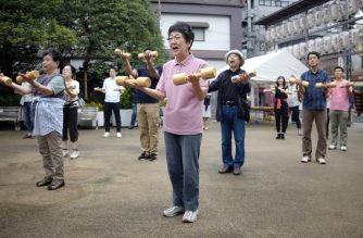 Elderly people work out with wooden dumb-bells in the grounds of a temple in Tokyo on September 19, 2016, to celebrate Japan's Respect for the Aged Day. / AFP PHOTO / KAZUHIRO NOGI