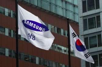 FILES: A Samsung flag (L) and South Korean national flag (R) flutter outside the Samsung building in Seoul on August 25, 2017. The heir to the Samsung business empire, including the world's biggest smartphone maker, awaited the verdict on August 25 in his corruption trial over the scandal that brought down president Park Geun-Hye. / AFP PHOTO / JUNG Yeon-Je