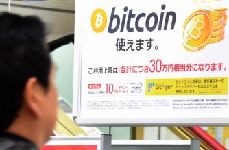 A man walks past a poster that informs customers that bitcoin can be used in this shop in Tokyo on January 06, 2018. Bitcoin is recognised as legal tender in the world's third-biggest economy and nearly one third of global bitcoin transactions in December were denominated in yen, according to specialised website jpbitcoin.com / AFP PHOTO / Toru YAMANAKA / TO GO WITH AFP STORY:  Japan-economy-bitcoin-forex, FOCUS by Ayaka MCGILL / Etienne BALMER