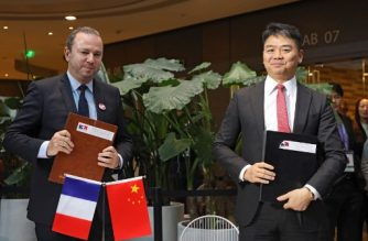 (File photo) CEO of JD.com Richard Liu (Qiangdong) (R) and Christophe Lecourtier (L), president of Business France, pose after signing an agreement during a meeting with business leaders and a visit by French President Emmanuel Macron (not pictured) at start-up incubator Soho3Q in Beijing on January 9, 2018. Chinese online retailer JD.com announced plans to sell French goods worth 2.4 billion USD to Chinese consumers over the next two years -- including high-end wine and cognac -- and spend 936 million USD on French industrial products. Macron is on the second day of his visit to the Chinese capital. / AFP PHOTO / ludovic MARIN