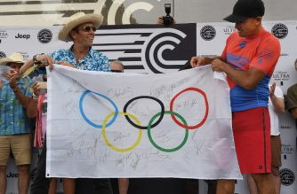 International Surfing Association President, Fernando Aguerre (L) and surfer Kelley Slater hold the Olympic flag during the WSL Founders' Cup of Surfing, at the Kelly Slater Surf Ranch in Lemoore, California on May 6, 2018.  Aguerre is credited with making surfing an Olympic sport at the 2020 Tokyo Olympics. - The two-day event brings twenty five of the worlds top surfers to compete on perfect machine-created waves in a half-mile long (.8kms) wave pool situated 100 miles (160.9kms) inland from the Pacific Ocean. (Photo by MARK RALSTON / AFP)