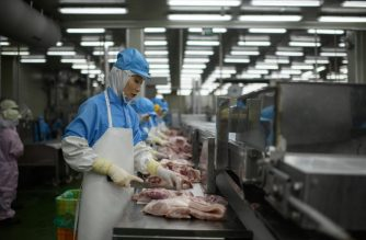 In a photo taken on August 28, 2018 cuts of meat are processed at a Spam factory in Jincheon. - From the front lines of war to a staple of institutional catering, Spam is rarely seen as a gourmet ingredient -- but the canned pink meat holds a unique position in South Korea as a top-selling holiday gift. (Photo by Ed JONES / AFP) / TO GO WITH STORY: SKorea-food-festival-spam, by Hwang Sunghee
