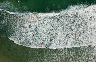 (FILES) This file aerial photo shows people paddling out as waves break at a beach in Hong Kong on December 31, 2017. New research in Hong Kong has found that UV filters commonly used in sunscreen are polluting surrounding waters and could endanger human health, one of the city's leading universities said on October 4. / AFP PHOTO / -