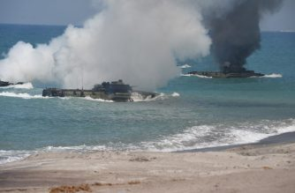 Amphibious Assault Vehicles (AAV) of the US marines emit white smoke during an amphibious landing exercise at the beach of the Philippine navy training center facing the south China sea in San Antonio town, Zambales province, north of Manila on October 6, 2018.  Japanese troops stormed a South China Sea beach in the Philippines on October 6 in joint military exercises with US and Filipino troops that officials said marked the first time Tokyo's armoured vehicles rolled on foreign soil after World War II.  / AFP PHOTO / TED ALJIBE