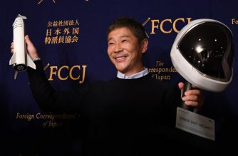 Yusaku Maezawa, entrepreneur and CEO of ZOZOTOWN and SpaceX BFR's first private passenger, poses with a miniature rocket and space helmet prior to start of a press conference at the Foreign Correspondents' Club of Japan in Tokyo on October 9, 2018. It was confirmed in September that Maezawa will be the first man to fly around the moon on a SpaceX rocket as early as 2023. / AFP PHOTO / Toshifumi KITAMURA