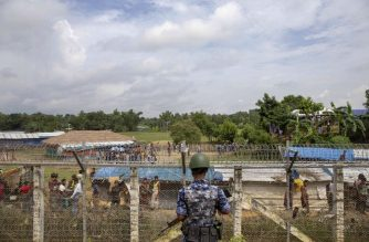 "(FILES) This file photo taken on August 24, 2018 shows Myanmar border guard police patrol watching over Rohingya refugees settlement in the ""no man's land"" zone between Myanmar and Bangladesh border as seen from Maungdaw, Rakhine state during a government-organized visit for journalists. Myanmar is ""unable and unwilling"" to conduct impartial investigations into allegations of genocide in Rakhine state, Yanghee Lee, a UN rights envoy who has been banned from the country said in a report on October 9, urging swift justice to avoid more violence. / AFP PHOTO / Phyo Hein KYAW"