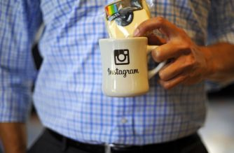 (FILES) In this file photo taken on June 19, 2013, an employee holds a cup with the Instagram logo at Facebook's corporate headquarters during a media event in Menlo Park, California. Instagram on October 9, 2018, added more weapons to battle cyber bullying, using artificial intelligence to scan photos for abusive content at the Facebook-owned service. / AFP PHOTO / Josh Edelson