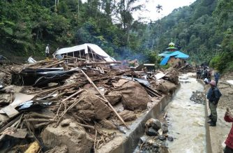 Villagers examine a site after it was hit by flash floods at the Saladi village in Mandailing Natal, North Sumatra on October 13, 2018. - At least 10 people are dead when heavy rain led to flash floods and landslide in Indonesia, an official said on October 13. (Photo by AGUS SALIM / AFP)