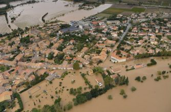 An aerial view taken on October 15, 2018 shows a flooded street in the city of Puichéric, near Carcassone, southern France. - Thirteen people have died after severe storms caused flash flooding across wide stretches of southwest France overnight, sweeping away vehicles and swamping homes, the interior ministry's rescue service said. (Photo by SYLVAIN THOMAS / AFP)