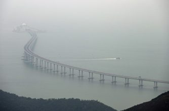 This general view shows a police boat patrolling waters around a section of the Hong Kong-Zhuhai-Macau Bridge (HKZM) in Hong Kong on October 23, 2018. - China's President Xi Jinping officially opened the world's longest sea bridge connecting Hong Kong, Macau and mainland China on October 23, at a time when Beijing is tightening its grip on its semi-autonomous territories. (Photo by Anthony WALLACE / AFP)