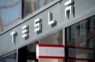 "This file photo shows the Tesla logo is seen outside of their showroom in Washington, DC, on August 8, 2018. - Tesla shares surged on Tuesday October 23, 2018, after a high-profile stock short-seller shifted gears to say the electric car maker is ""destroying the competition."" (Photo by SAUL LOEB / AFP)"