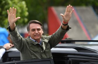 Jair Bolsonaro, far-right lawmaker and presidential candidate for the Social Liberal Party (PSL), waves to supporters, during the second round of the presidential elections, in Rio de Janeiro, Brazil on October 28, 2018. - Brazilians will choose their president today during the second round of the national elections between the far-right firebrand Jair Bolsonaro and leftist Fernando Haddad (Photo by MAURO PIMENTEL / AFP)