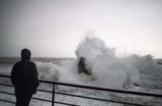 A man looks at a rough sea in the village of Monterosso in the Liguria region, on October 29, 2018. - Ahead of bad weather with wind gusts up to 100 km/h on the coast and 150 km/h in the mountains, and a total of precipitation in a few days equivalent to the rainfall of several months, Italy was on the red alert in the northern regions and orange over a good part of the rest of the peninsula. (Photo by Marco BERTORELLO / AFP)