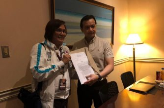 Opposition Senator Antonio Trillanes IV poses together with the sheriff of the Makati regional trial court branch 148 showing a copy of the court's resolution denying the Department's Justice's motion to issue an arrest warrant against Trillanes.  (Photo courtesy office of Senator Antonio Trillanes IV)