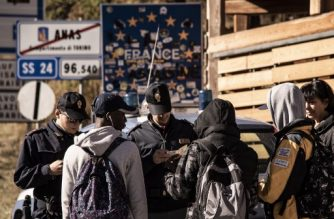 Italian Police border officers (L and 3rdL) check the papers of three African migrants on October 21, 2018 in the Alpine border town of Claviere, some 100 kilometers west of Turin. - Italy's Interior minister Matteo Salvini sent police on October 20 to Claviere, following an ongoing argument with French authorities over the alleged return of migrants deposed by French police on the Italian side of the border in Claviere. (Photo by MARCO BERTORELLO / AFP)