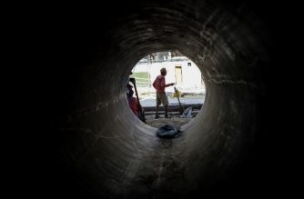 A worker is seen through a culvert at a road construction site on the Philippine island of Boracay on October 25, 2018. - The Philippines re-opens its crown jewel resort island Boracay to holidaymakers on October 26, after a six-month clean up aimed at repairing the damage inflicted by years of unrestrained mass tourism. (Photo by NOEL CELIS / AFP)