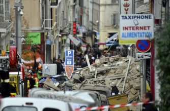 Policemen and firemen stand guard inside a security perimeter set after a building collapsed, on November 5, 2018 in Marseille. (Photo by GERARD JULIEN / AFP)