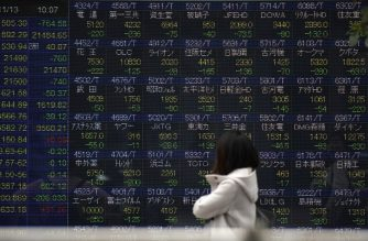 A pedestrian looks at an electronics stock indicator at the window of a security company displaying the current rate of Tokyo Stock Exchange in Tokyo on November 13, 2018. - Tokyo stocks dived more than three percent shortly after the open on November 13, with investors discouraged by a plunge in US shares on fears over demand in the tech sector. (Photo by Toshifumi KITAMURA / AFP)