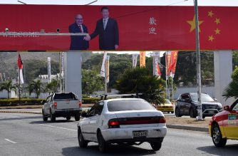 A billboard featuring Papua New Guinea's Prime Minister Peter O'Neill (top L) shaking hands with China's President Xi Jinping is displayed ahead of the Asia-Pacific Economic Cooperation (APEC) summit in Port Moresby on November 15, 2018. (Photo by Saeed KHAN / AFP)