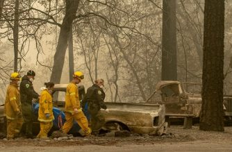 Rescue workers carry a body away from a burned property in the Holly Hills area of Paradise, California on November 14, 2018. - Firefighters backed by air tankers and helicopters battled California's raging wildfires for a seventh day on Wednesday as the authorities in the worst-hit county released a list of over 100 missing people. At least 51 deaths have been reported so far from the deadliest wildfires in California's recent history and body recovery teams were going house-to-house with cadaver dogs in Paradise. (Photo by Josh Edelson / AFP) / ALTERNATIVE CROP
