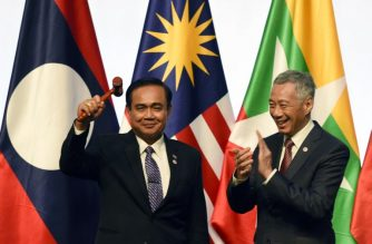 Singapore's Prime Minister Lee Hsien Loong applauds as Thai Prime Minister Prayut Chan-O-Cha holds up the gavel during the closing ceremony of the 33rd Association of Southeast Asian Nations (ASEAN) summit in Singapore on November 15, 2018. (Photo by Roslan RAHMAN / AFP)