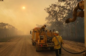 Firefighters refill their water from a water tanker in Pacific Drive in Deepwater National Park area of Queensland on November 28, 2018. - Thousands of people were being evacuated from their homes in northeast Australia as bushfires raged across Queensland state amid a scorching heatwave. (Photo by ROB GRIFFITH / AFP)