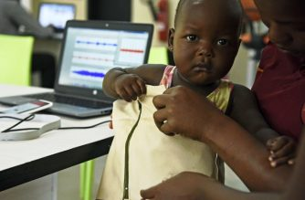 """Telecommunications engineer Olivia Koburongo fits a child with the mama-ope kit at the Makerere University of Public Health in Kampala on January 16, 2017. - A team of Ugandan engineers has invented a """"smart jacket"""" that diagnoses pneumonia faster than a doctor, offering hope against a disease which kills more children worldwide than any other. (Photo by ISAAC KASAMANI / AFP)"""