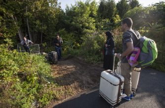 RCMP officers speaks with migrants as they prepare to cross the US/Canada border illegally near Hemmingford, Quebec, August 20, 2017. - Thousands of refugees have been streaming across the Canada/US over the past few months, overwhelming the government's capacity to house them while their claims are processed. (Photo by Geoff Robins / AFP)