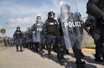 """HIDALGO, TX - NOVEMBER 05: U.S. Customs and Border Protection (CBP), agents in riot gear take part in a training exercise at the international port of entry on the U.S.-Mexico border on November 5, 2018 in Hidalgo, Texas. Days before, U.S. Army soldiers put up razor wire at the same location as part of """"Operation Faithful Patriot."""" President Donald Trump ordered troops to the border ahead of midterm elections and weeks before the possible arrival of a migrant caravan.   John Moore/Getty Images/AFP"""